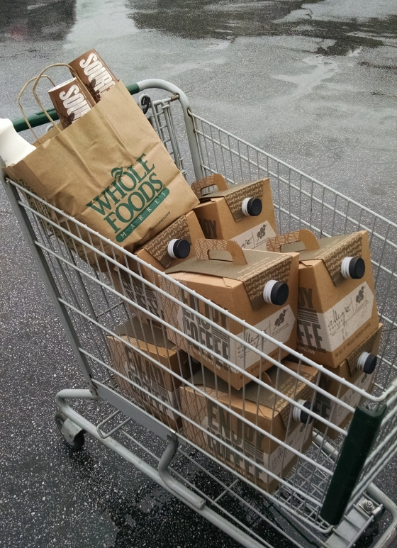A weird picture of coffee boxes in a shopping cart in a rainy parking lot.